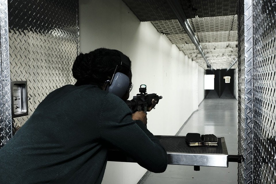 A rear view of a woman shooting in a shooting range
