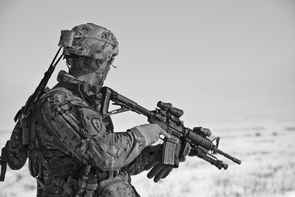 A grayscale photograph of a soldier holding an M4 Carbine