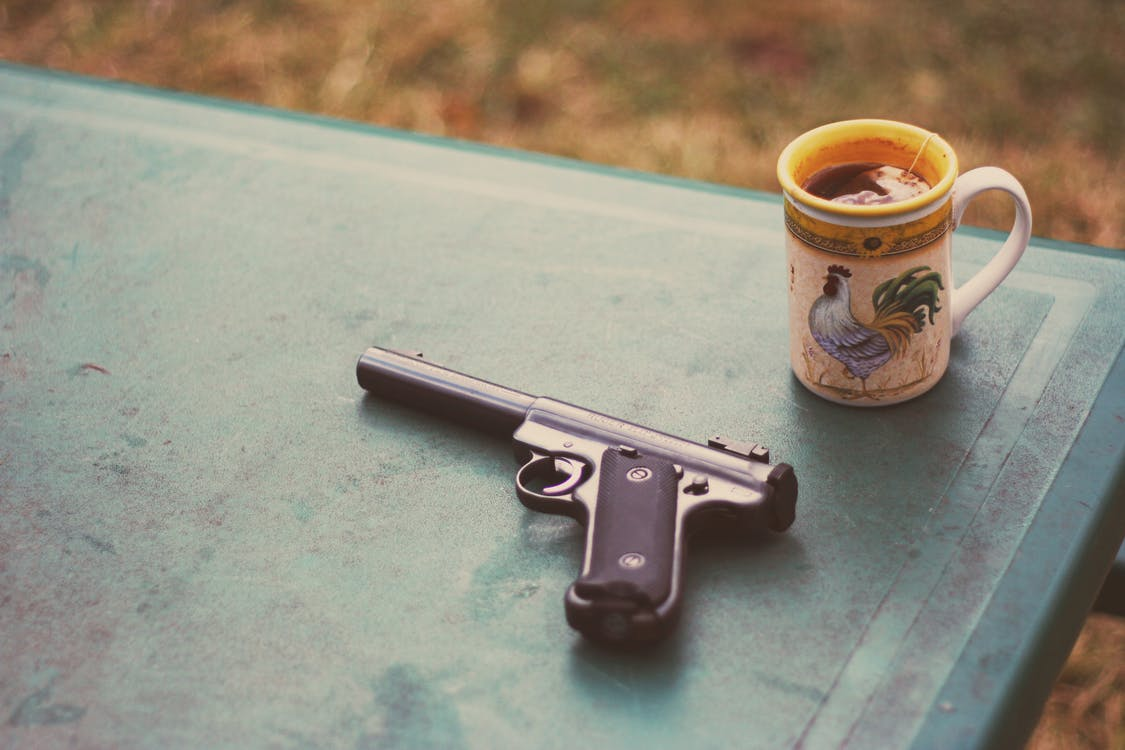 a handgun on a table next to a mug of black coffee