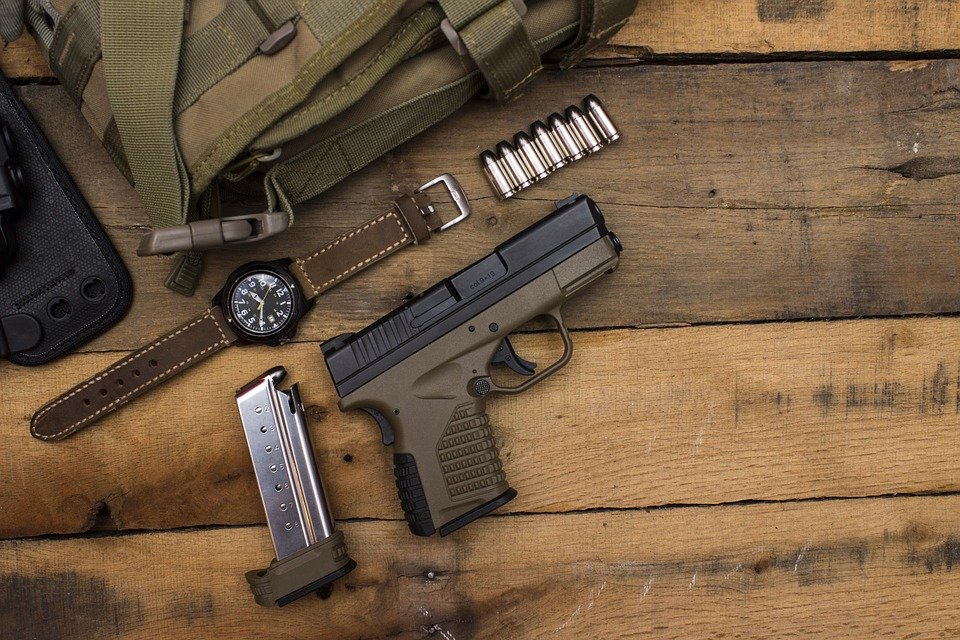 A watch, a handgun, a razor and a bag on a wooden table