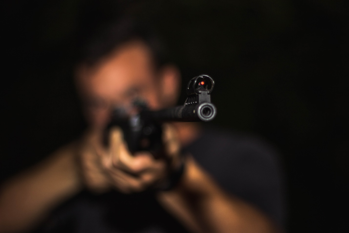 An out of focus image of a man in a black shirt holding a rifle